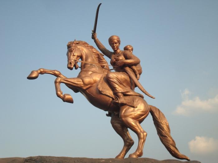 В Индии немало памятников Лакшми-Бай. На этом она изображена с приёмным сыном своего покойного мужа за спиной.